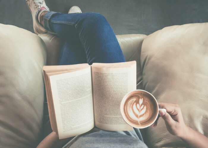 person reading book with coffee