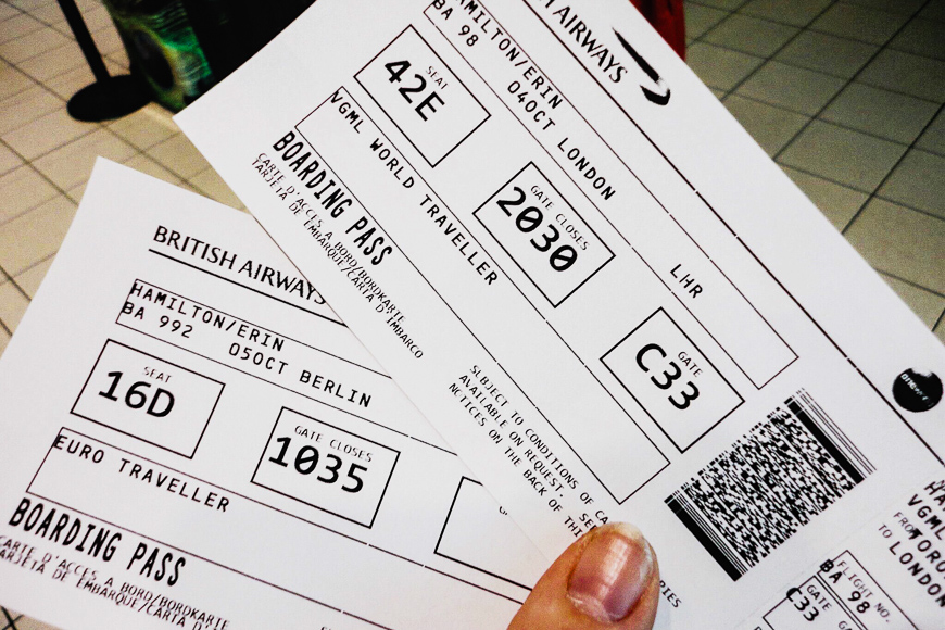person holds two paper boarding passes