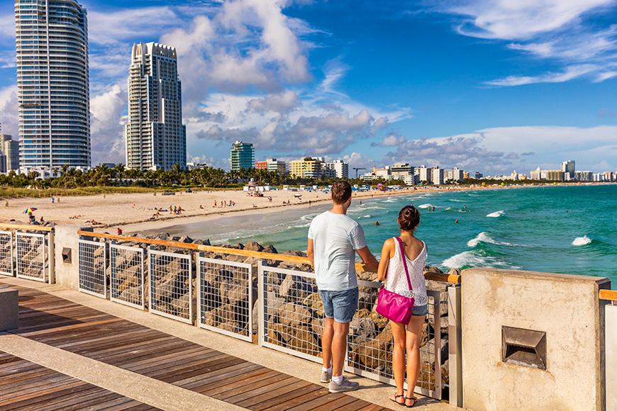 Miami beach tourists couple walking in South Beach, Miami, Florida.