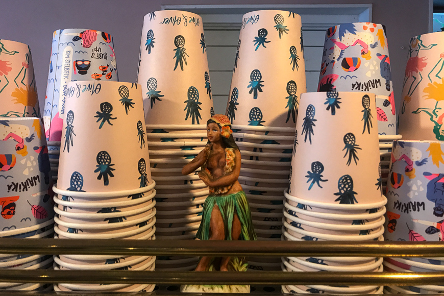 Hula girl statue next to cups