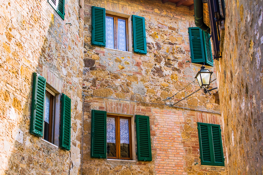 fragment of a brick wall of an old historical town in Italy with windows with green wooden shutters and a sunlit street lamp