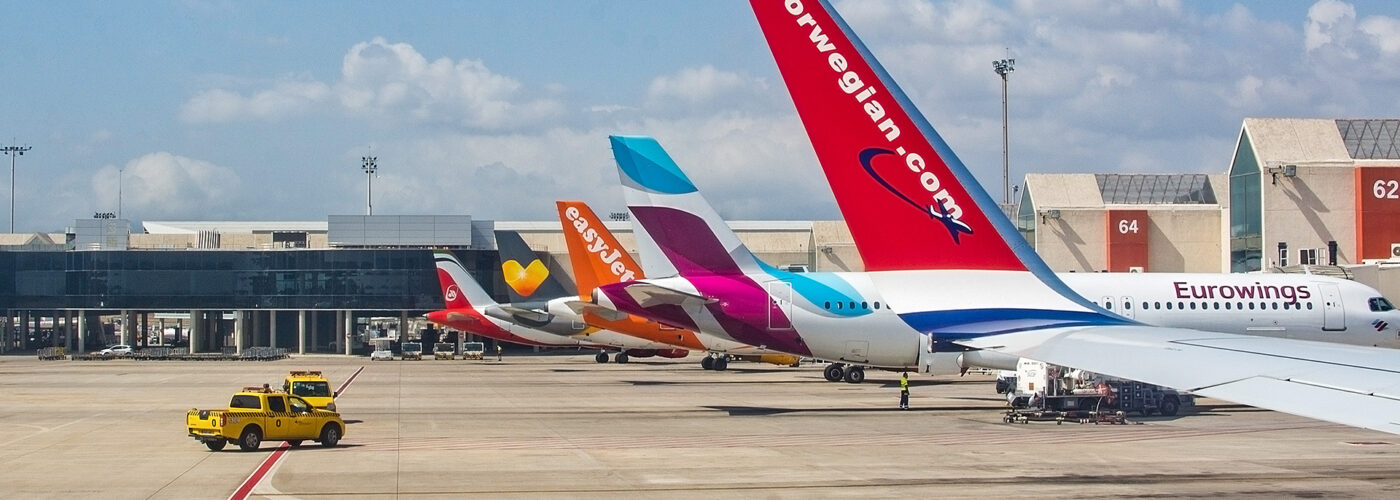planes parked at airport in a row. Airplane tail fins from Norwegian, Eurowings, Easyjet on the tarmac