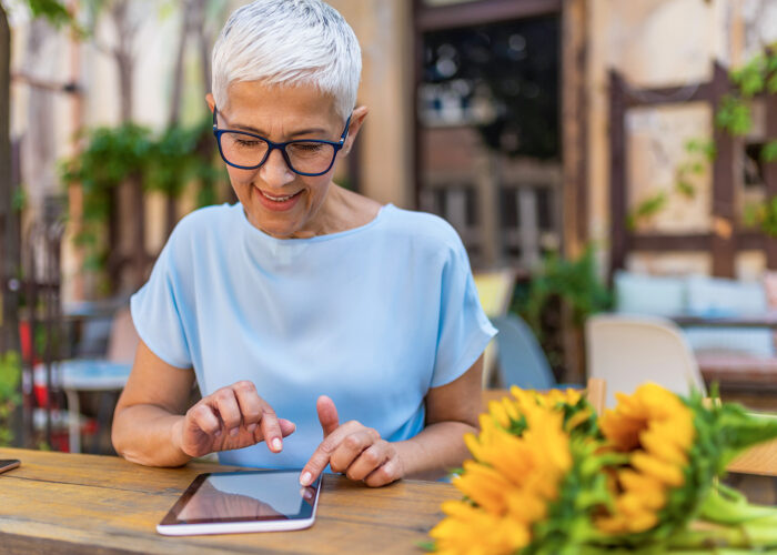 smiling senior woman booking travel on ipad in cafe