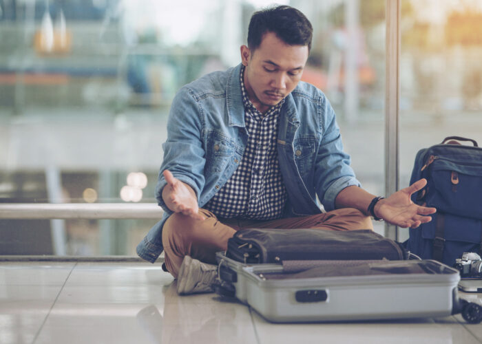 man looking at empty suitcase worried