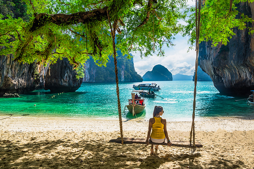 woman relaxing on wooden swing under tree tropical beach, koh lao lading island, andaman sea, krabi province, thailand