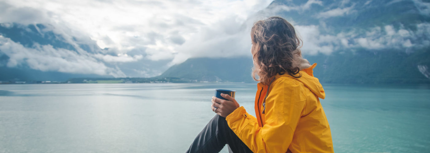 Woman drinking from mug and looking out on fjord