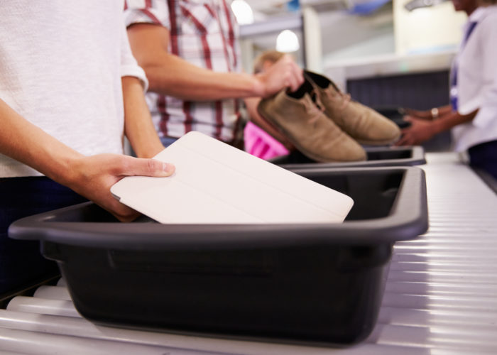 People placing items in bins at airport security
