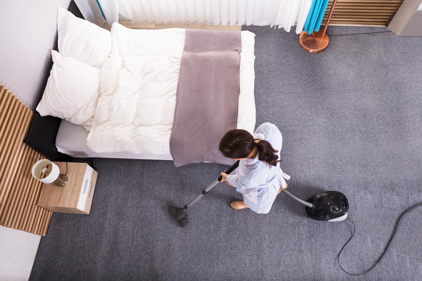 Housekeeper Cleaning Carpet With Vacuum Cleaner In Hotel Room