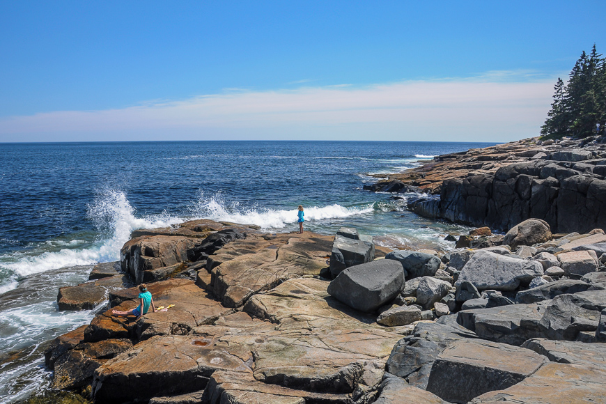 Children watching waves to hit the rocky coast of Maine at Schoodic Point