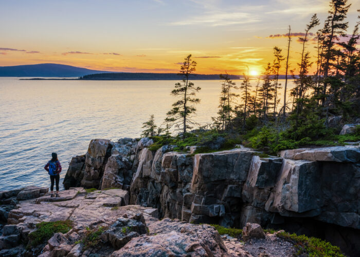Female Hiker watching a sunset in Acadia National Park, Maine