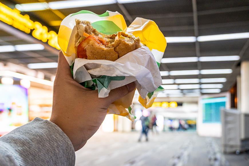 Man hand holding Burger at airport terminal