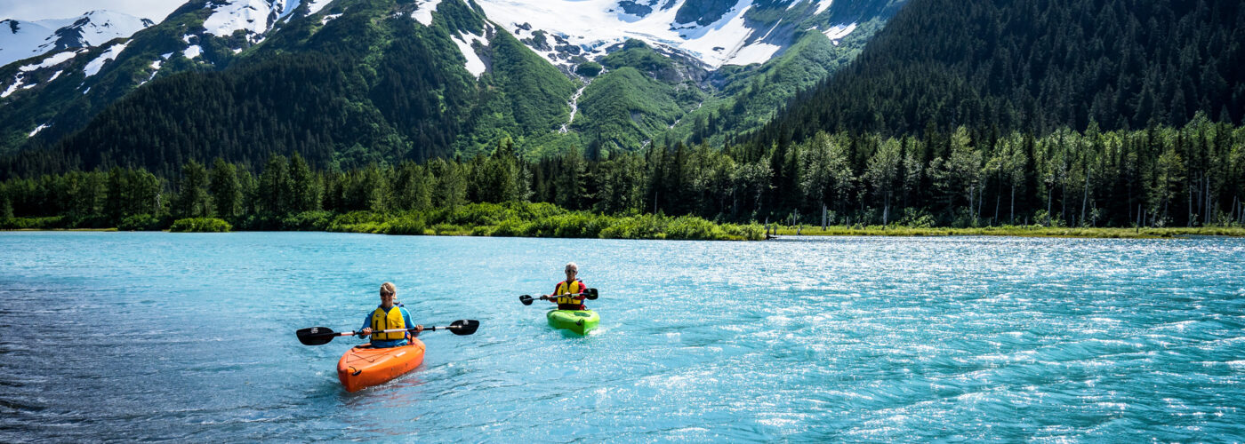 two people kayak in front of a glacier in anchorage alaska