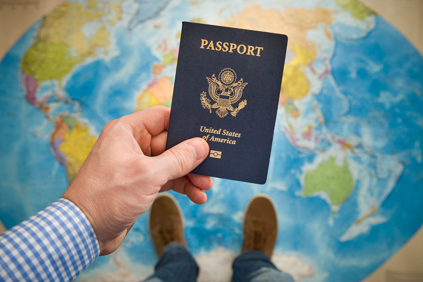 man holding U.S. passport over world map