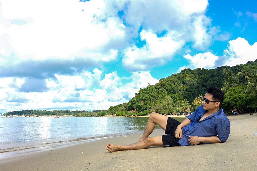 Asian man lying down on the beach relaxing and seeing beautiful sea view on his holidays on paradise island.