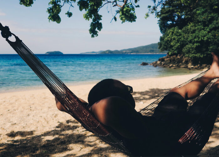 man sits in hammock on a quiet beach