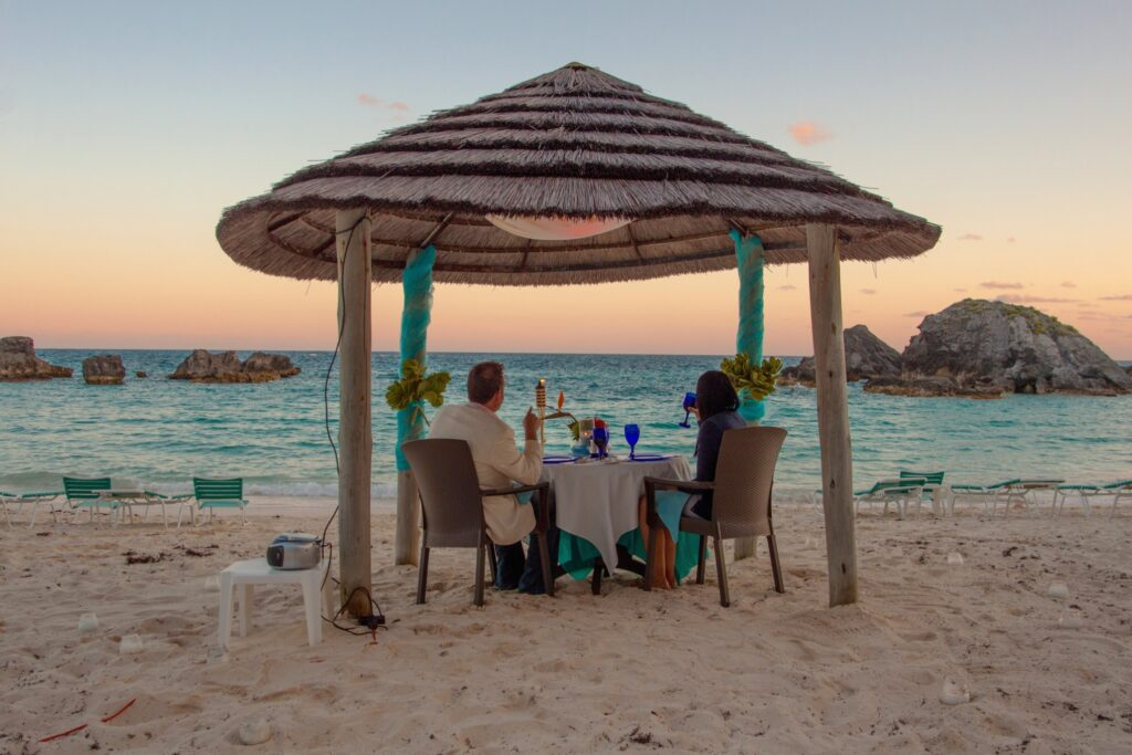 couple on beach in bermuda having dinner
