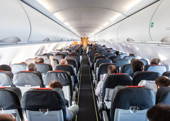 Interior of commercial airplane with unrecognizable passengers on their seats during flight