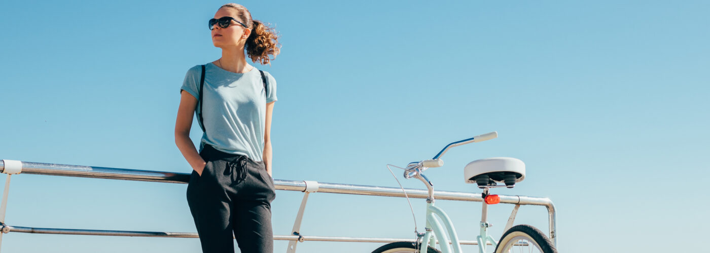 Woman on boardwalk standing with hands in pants pocket.