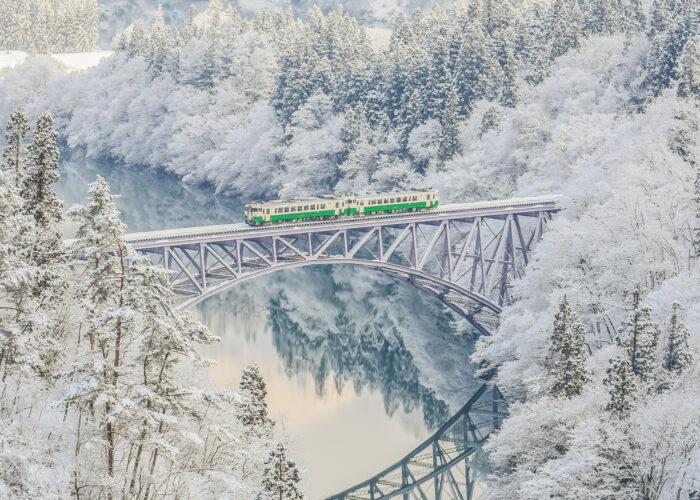 train passing over bridge in japan winter backdrop