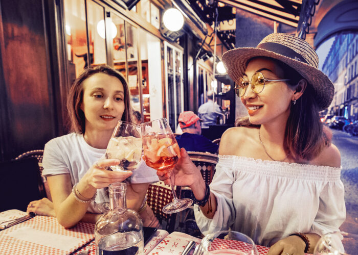 Two mixed race girls friends clinking glasses while enjoying an celebrating moment in cafe at evening time