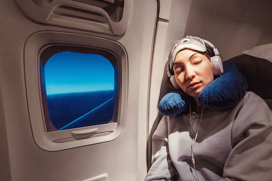 Asian girl sleeping in her seat on the plane near the window in a mask and with a pillow to sleep