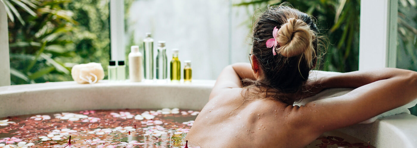 women in bath filled with rose petals and essential oils on the side