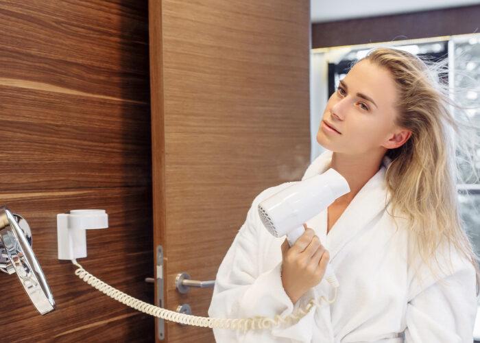 woman hotel room drying hair bathrobe bathroom