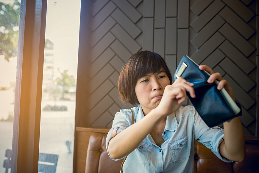 Asian woman with no money in coffee shop she looking empty pocket