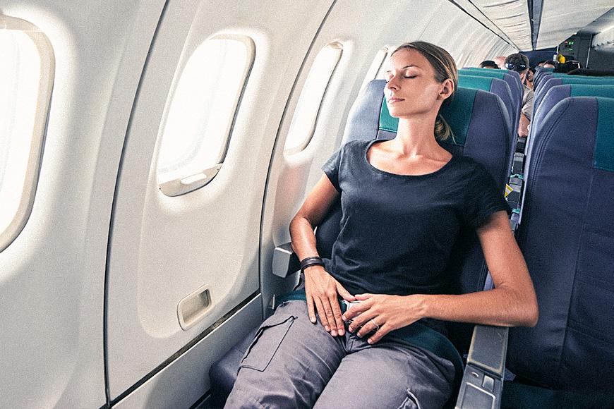 woman reclining seat flight plane window