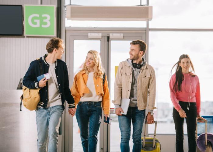 Four friends walking to an airport terminal