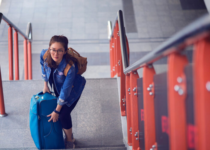 Young woman going up the stairs with her heavy suitcase