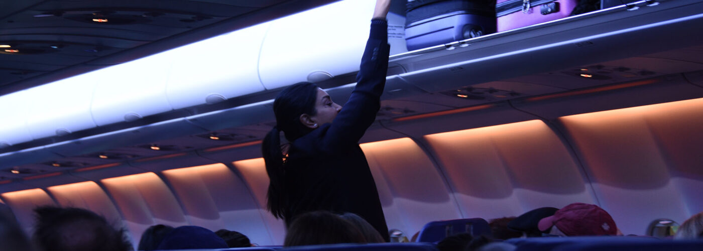 flight attendant closing overhead bin.