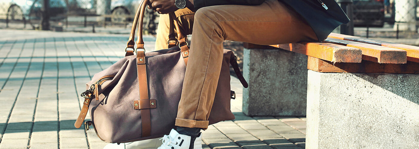 man holding weekender bag sitting bench city