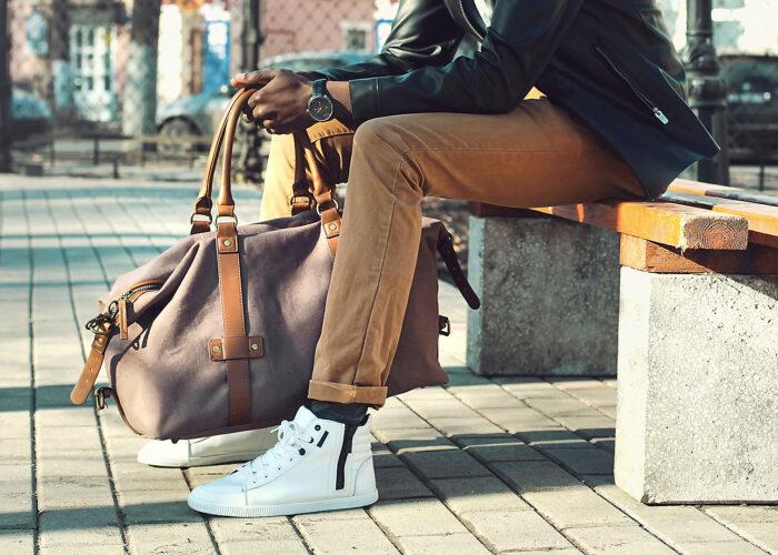 man holding weekender bag sitting bench city