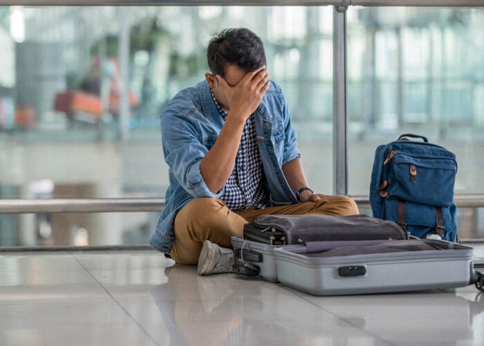 man sitting on floor at airport with open luggage lost item