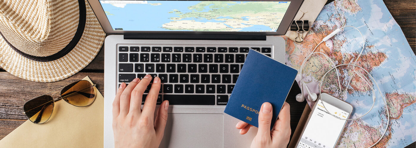 Female hand holding a passport over a laptop