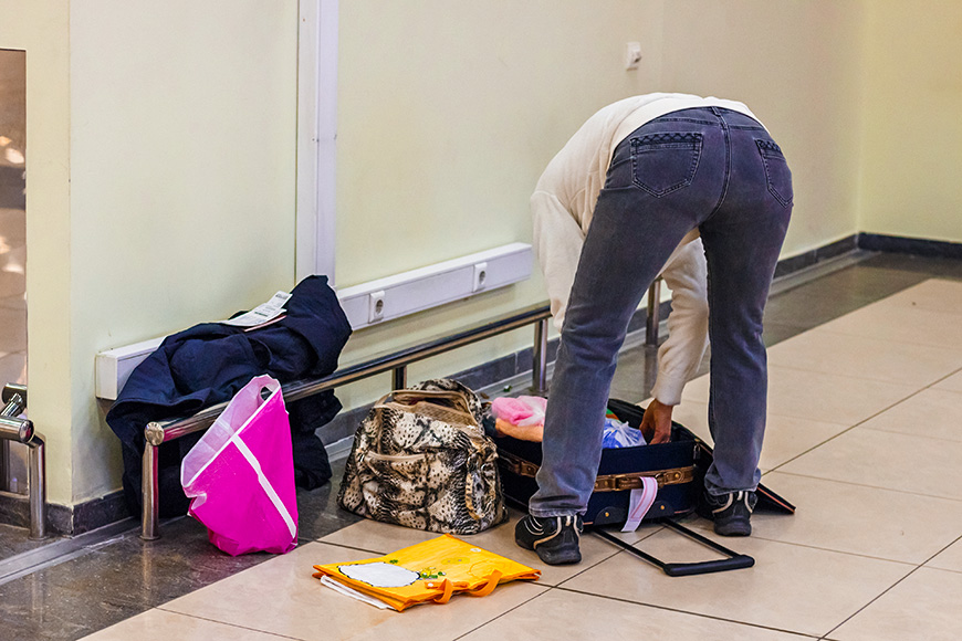 Passenger parses things out of a suitcase at the airport before departure