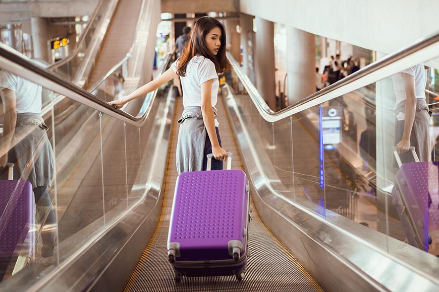 Asian woman traveler walking on escalator to airplane