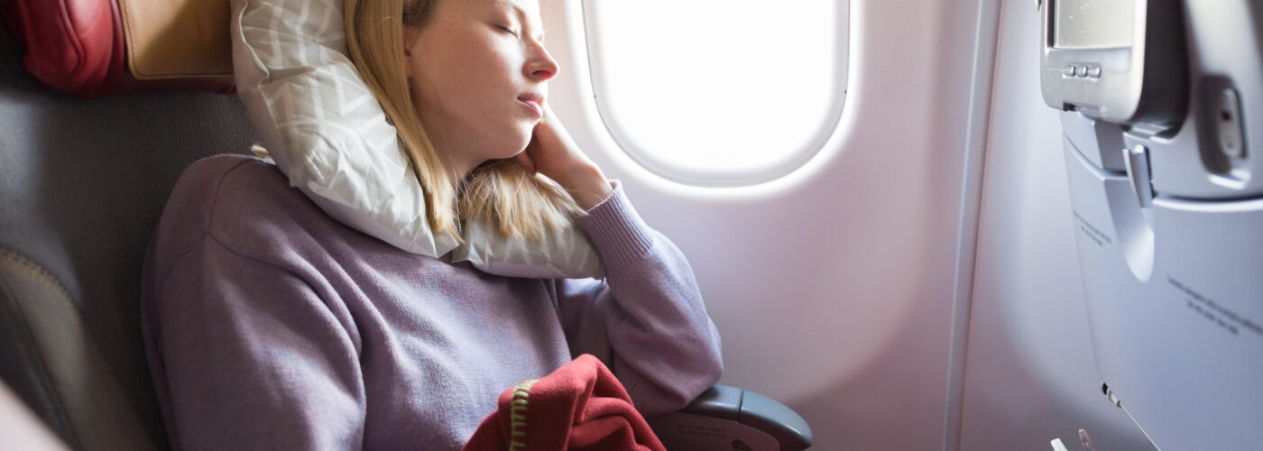 woman sleeping on plane in window seat