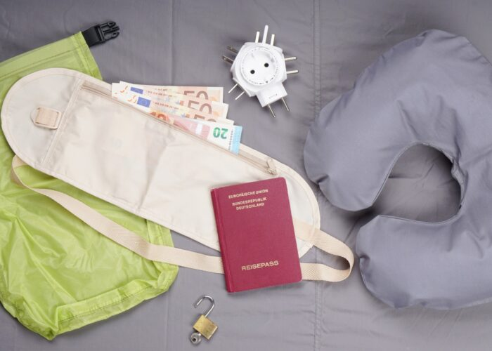 flat lay of travel related items including money belt neck pillow charger passport lock