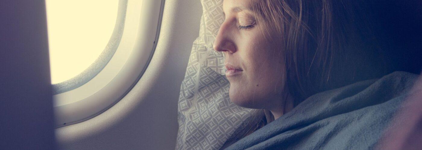 woman sleeping with blanket on plane