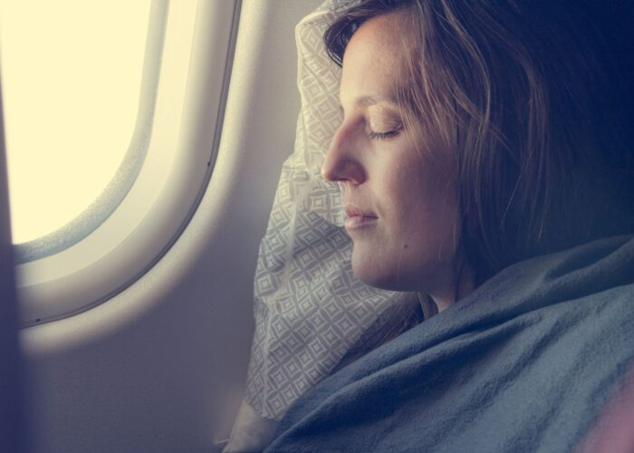 woman sleeping with blanket on plane