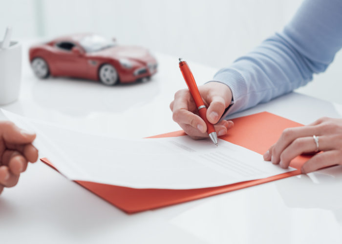 Person signing car rental agreement with a small model car in the background