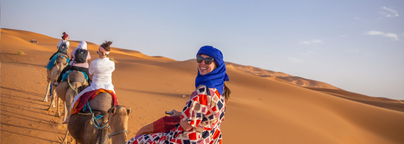 travelers ride on camels in shara desert Staff FOC trip to Morocco Uncovered (XMKC)