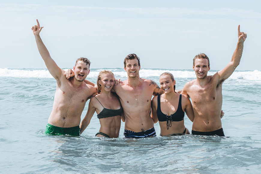 Kiwi Vibes tour company 4 people in ocean waving