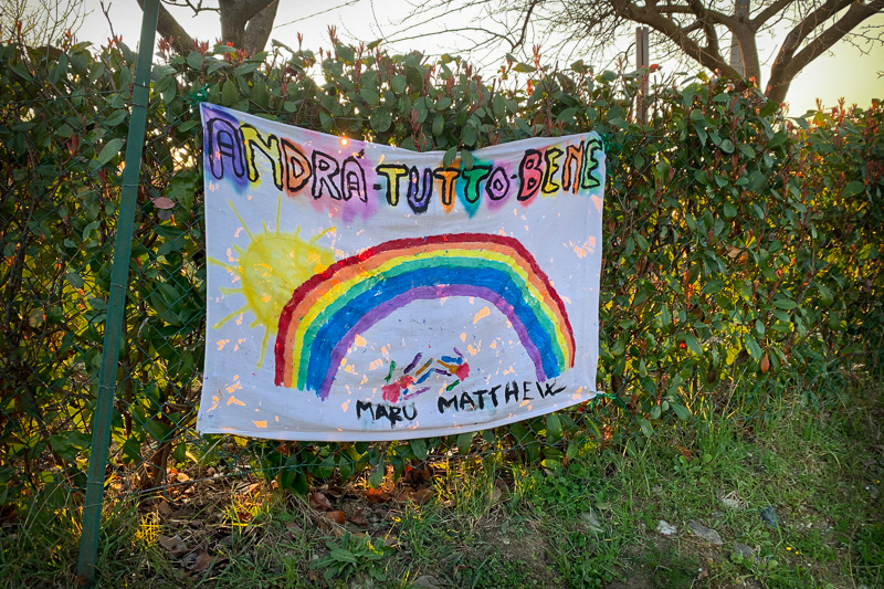 "drawings of rainbows with the phrase ""Andrà tutto bene"