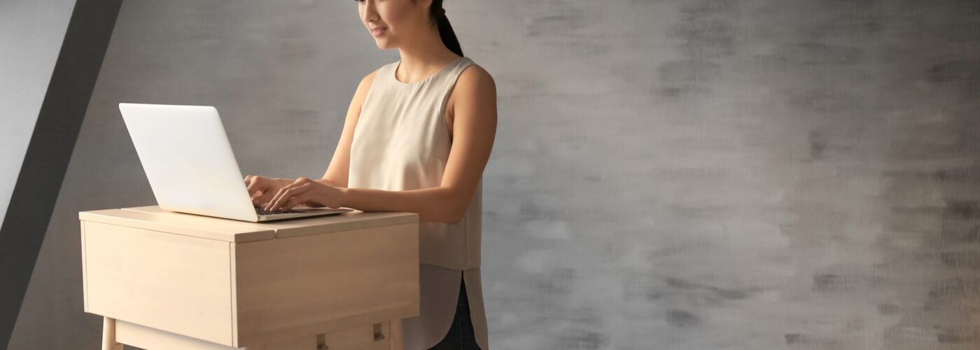 woman typing at standing desk