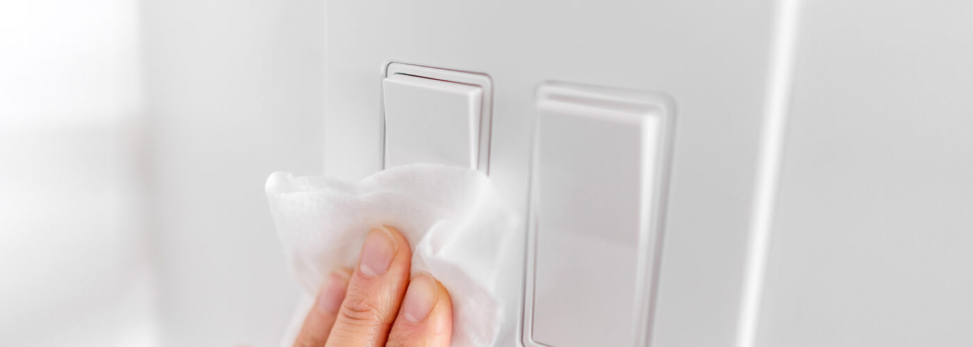 hands wiping lightswitch with disinfectant wipes