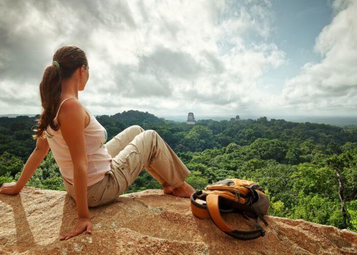 woman traveler looking at tikal maya ruins in guatemala.