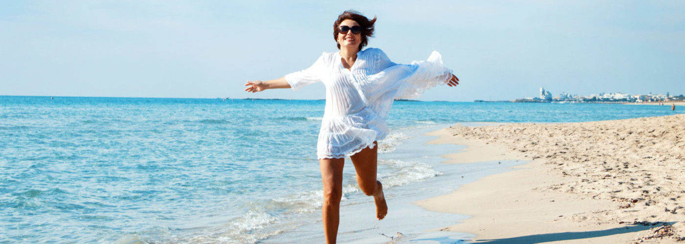 Woman running toward camera on beach in white beach cover up